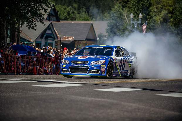 NASCAR legend Jimmie Johnson does a burnout on Main Street during Aspen's Fourth of July parade on Tuesday.
