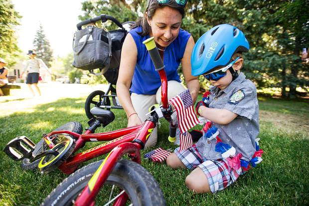 Henry, 3.5, and his mom Lane Shea prep his bike in Paepcke Park before the start of the parade in Aspen on Tuesday.