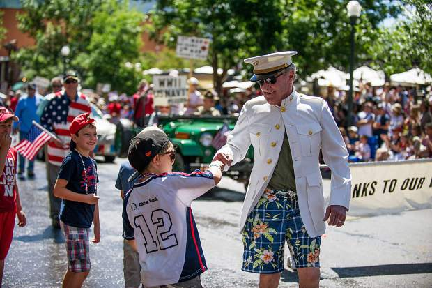 A veteran shakes hands with children on Hyman Ave. during the parade on Tuesday.
