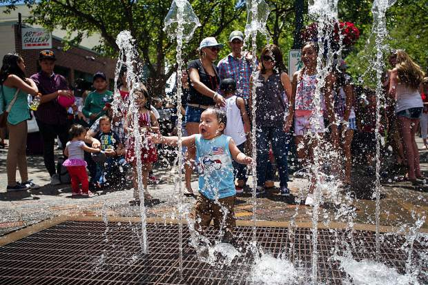 A little boy plays in the fountains in Aspen's pedestrian mall on Tuesday.