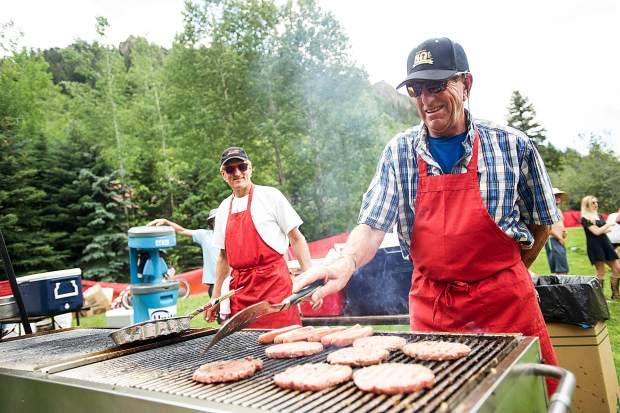 A man flips burgers at the AVSC picnic in Koch Park in Aspen on Tuesday.