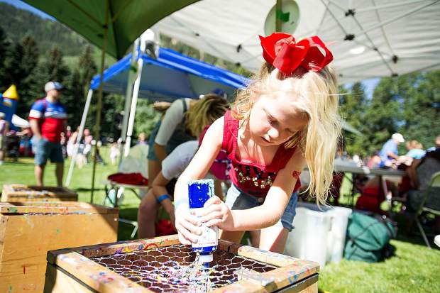 Eleanor Ritchie, 5, makes a tie-dye frisbee in Paepcke Park Tuesday morning.