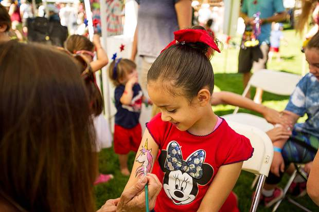 Monse gets a unicorn painted on her arm at Paepcke Park on Tuesday.