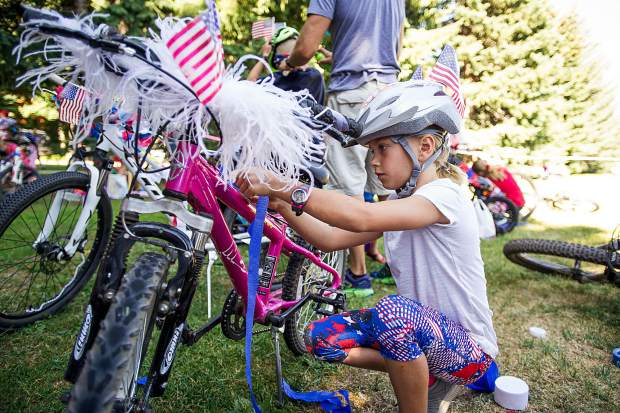 MeKenna Bruno, 8, of Fort Collins prepares her bike at Paepcke Park before the parade in Aspen on Tuesday.