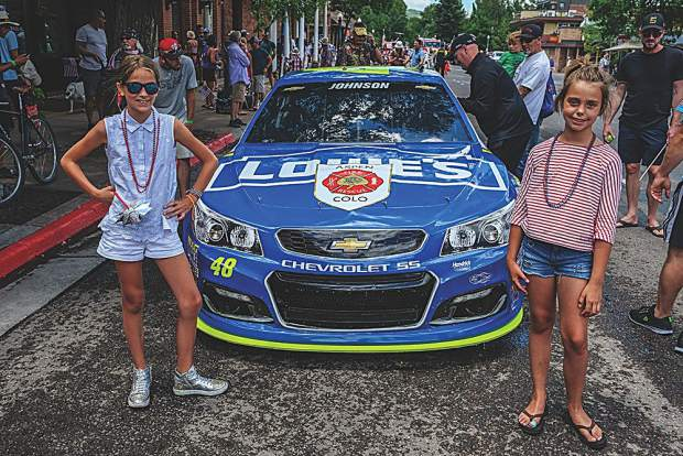 Sisters Gemma and Leila Baker strike a pose with Jimmie Johnson's No. 48 race car. George Baker photo.