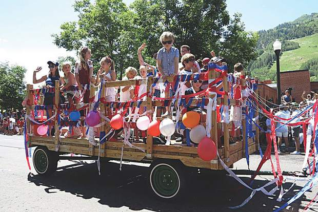 A wagon full of adorable kids rolls through the parade.