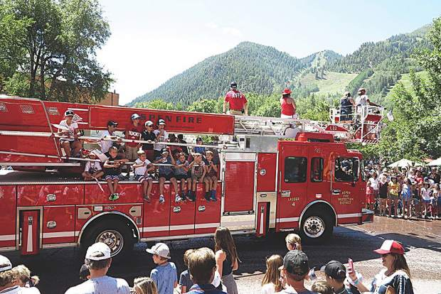 Future firefighters flank the sides of an Aspen Volunteer Fire Department truck in the parade.