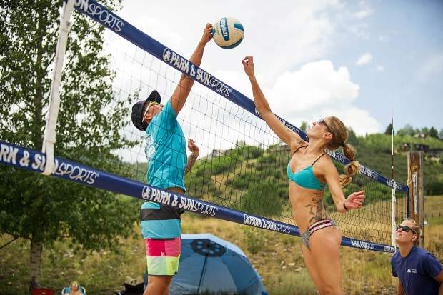 Jenny Li, left, tries to spike the volleyball while Liz Card blocks in the women's league of the doubles sand volleyball tournament.