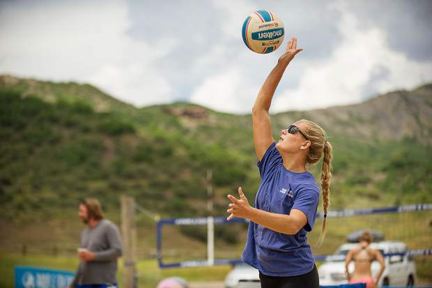 Katie Pyles serves the volleyball in the women's league of the doubles sand volleyball tournament.
