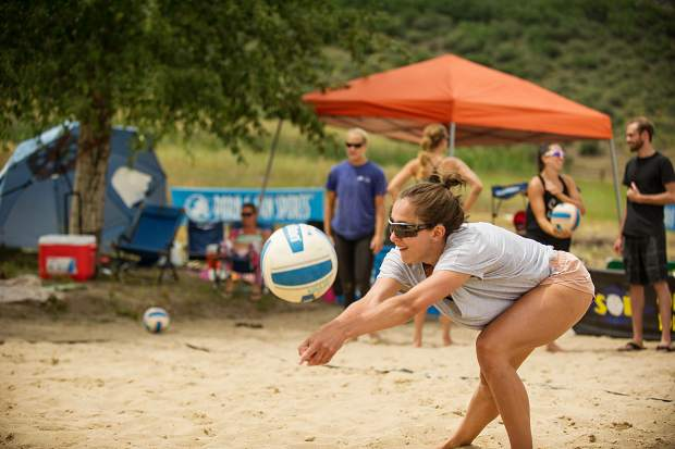 A competitor bumps the volleyball for practice at the women's league of the doubles sand volleyball tournament.