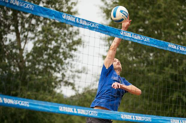 Jeff Bunge spikes the volleyball at the men's league of the doubles sand volleyball tournament on Saturday.