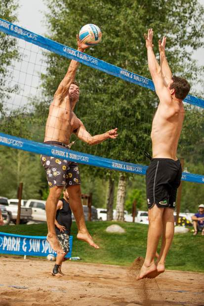 Jordan Weber spikes the volleyball while Jurgen Koenig blocks the shot at the men's league of the doubles sand volleyball tournament on July 22.