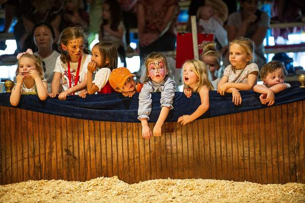A group of children watch the circus on the edge of the circus ring.