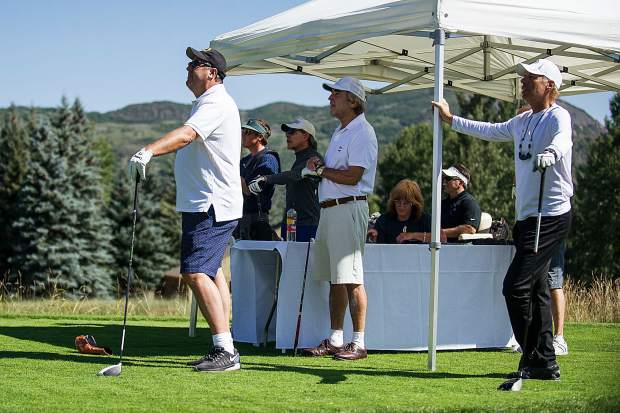 Vince Gill, left and his group watch as Bobby Bradley tees off of hole 11 at the Snowmass Club for Challenge Aspen benefit known as the Vince Gill and Amy Grant 14th Anniversary Gala and Golf Classic on Tuesday.