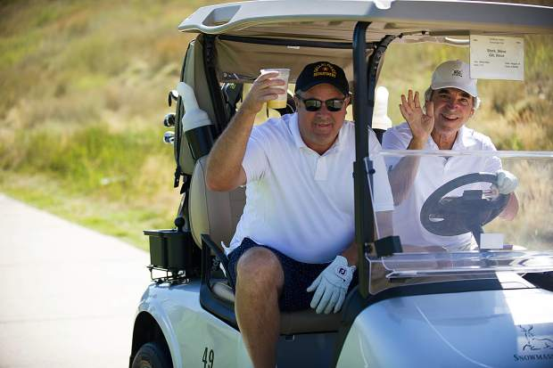 Vince Gill, left and his friend Steve Stark drive off in their cart after teeing off of hole 11 at the Snowmass Club for Challenge Aspen benefit known as the Vince Gill and Amy Grant 14th Anniversary Gala and Golf Classic on Tuesday.