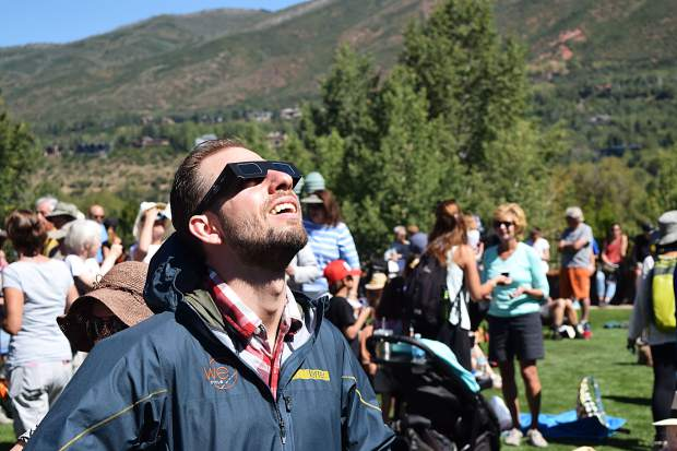 An eclipse watcher strikes a common pose seen Monday at Galena Plaza.