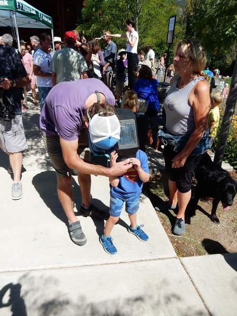 A young eclipse viewer dons special eyewear at Basalt Regional Library.