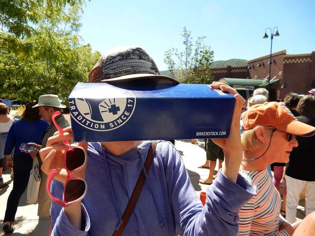 A spectator uses a box with a pin hole to check the eclipse's progress at Basalt Regional Library.