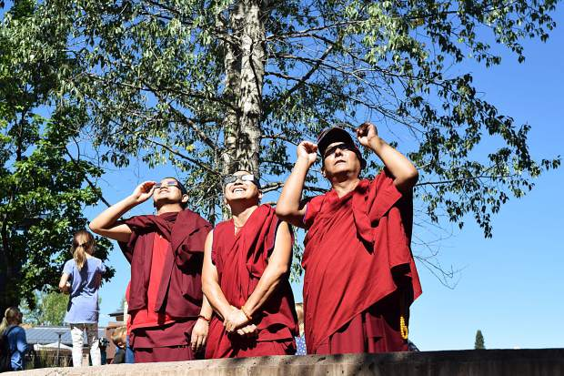 Monks of the Gaden Shartse Monastery check out the eclipse Monday in the outdoor area near the Pitkin County Jail, which is near the viewing party held at the Pitkin County Library.