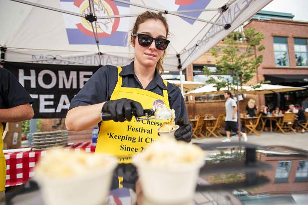 Amy Fritzsche of Home Team BBQ fills a mac and cheese cup with their smoked gouda mac and cheese for the 7th Annual Mac and Cheese Festival held on