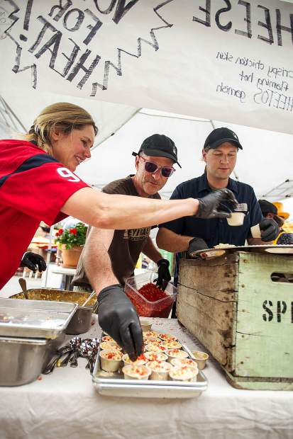 Wendy Mitchell and husband Todd, center, fill buffalo chicken mac and cheese cups for the 7th Annual Mac and Cheese Festival held on