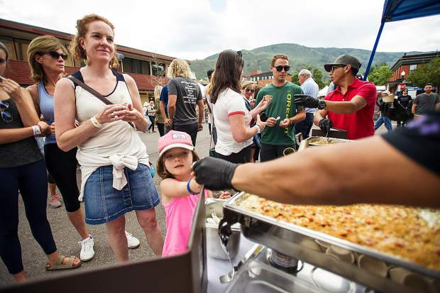 Thea Rioux, 5, gets handed mac and cheese from the Cache Cache booth for the 7th Annual Mac and Cheese Festival held on