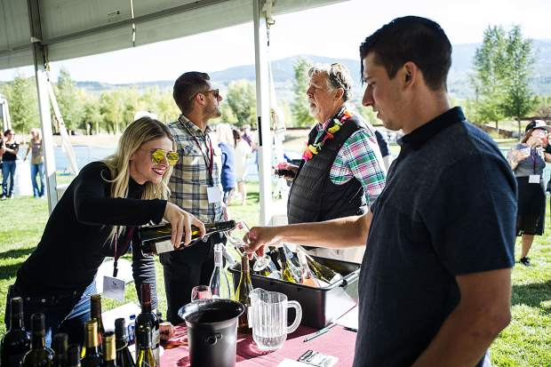 Kaley Davidson of Pioneer Wines pours a sample tasting for wine festival-goer Nate Soucie.