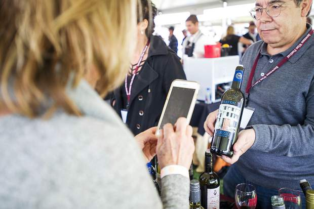Mano Scanu of Lenardo Locascio Wines holds up a bottle of wine for a guest to snap a photo at the Snowmass Wine Festival Grand Tasting held on Saturday at the Town Park.