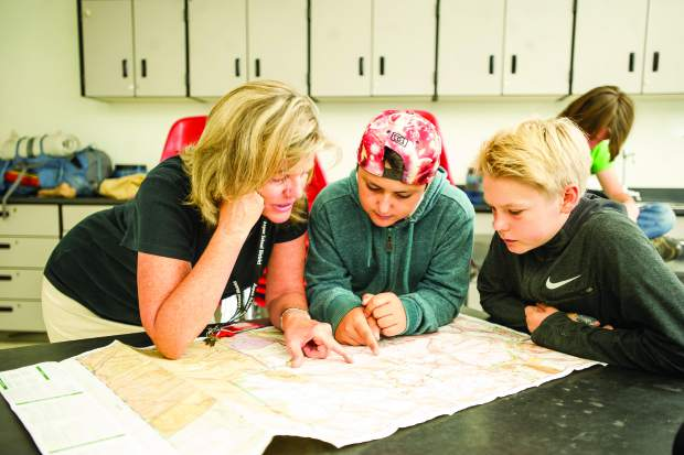 Diane Godfrey points out where the 8th graders will be exploring on a map to Lian Lilah, 13, left, and Jake Morgan, 13.