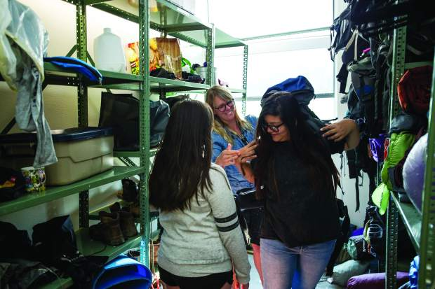 Marilyn Soriano, right gets fitted for a backpack from her teacher Ms. Dana Berro.