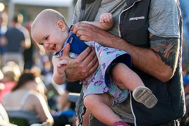 A baby giggles after getting picked up by her dad Saturday in Snowmass for the JAS Aspen Snowmass concerts.
