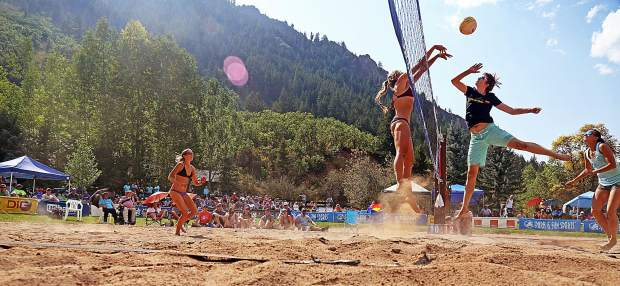 Cassie House, middle left, greets Nola Basey at the net during the women's open final Monday at the 45th annual MotherLode Volleyball Classic at Koch Lumber Park in Aspen.