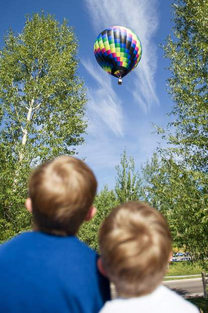 Two little brothers watch a balloon float by at the Snowmass 42nd Annual Balloon Festival on Friday morning.