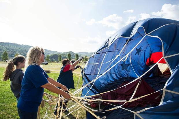 Jennie Jansson, right, Delaney Pendleton and her grandmother May Bell Pendleton work on packing up their hot air balloon Spirit in the Sky at the Snowmass 42nd Annual Balloon Festival on Friday morning.