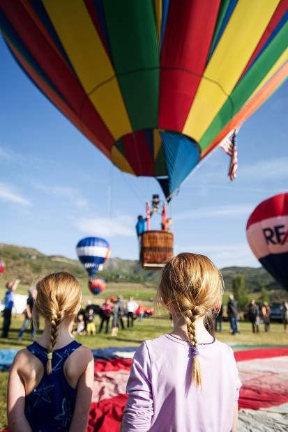 Siri, 6, and Bergen Loeffler, 4, watch a pilot take off in Snowmass at the 42nd annual balloon festival on Saturday.
