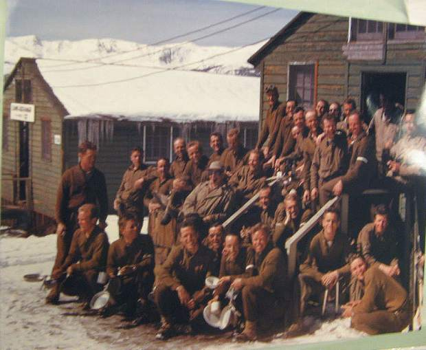 Color photograph of Tenth Mtn. Division soldiers posing at Camp Hale. They are in front of a building, and another building (Camp Exchange) is visible in the background. Several of the men hold kitchen utensils. There is snow on the ground. 1944-