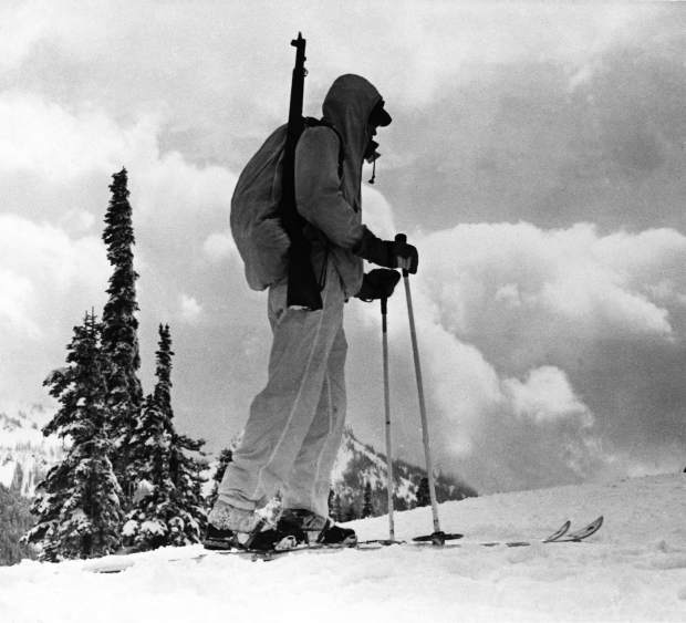 One b/w photograph and negative of a Tenth Mountain Division soldier in full uniform, wearing skis and carrying a backpack with a gun. 1955-