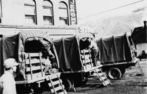 One b/w photograph of three army trucks parked outside of the Hotel Jerome, fully loaded to go to Camp Hale. Part of the hotel sign is visible, and also three of the lower windows. One man is standing on the bumper of the middle truck, and another man is visible in the lower left corner. The photo is labeled