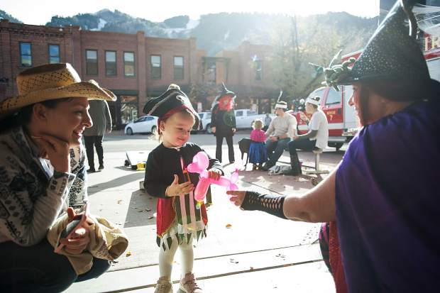Meera Bradhan, 20 months, receives a balloon animal at the Aspen volunteer fire department on Tuesday for their Ellks Lodge Hallooween