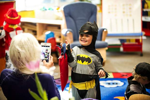 Merric Lutz-Sladdin, 4, poses for a photo with his new reading book bag on Tuesday at the Yelowbrick dayecare center for Halloween.