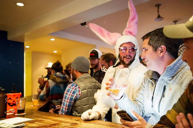 Sean Clark, right, and a dressed up bunny grab beers at Aspen Brewery's last night at their Hopkins' location on Tuesday.