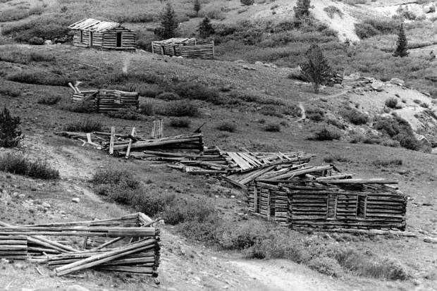One b/w photograph looking down Aspen Avenue (Main street) of the Ghost Town of Independence. In the foreground of the photograph on the right side of the street is a cabin with walls still standing which can be seen from the side. Along the same side is a row of collapsed structures. On the left side of the road is a single structure which has at least three walls still standing but no roof. In the background of the photograph there are two standing cabins standing parallel to each other. The cabin on the left has a partial roof still intact while the right cabin appears to have wood still attached to the roof. Published in the Aspen Times July 3, 1980 on page 1-b.