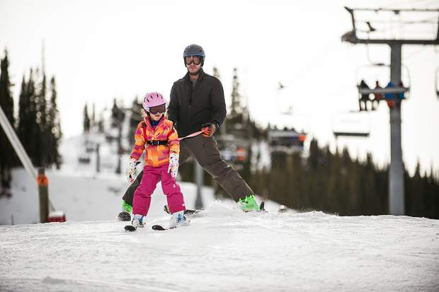 A dad and daughter ski down Aspen Mountain on opening day Thursday.