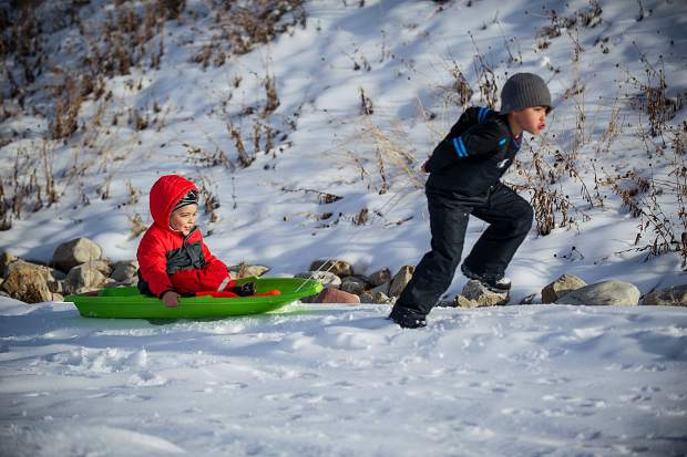 Julian Mirabal, 6, pulls his brother Christian, 4, in a sled next to Fanny Hill on Snowmass for their opening day on Thanksgiving.