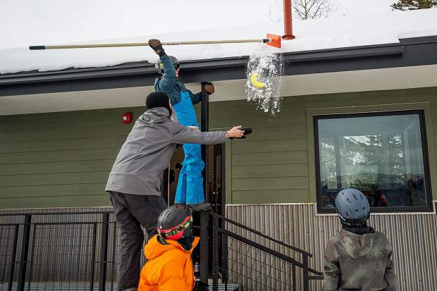 Sean Connelly, 15, pulls a banana down from the top of the ski patrol shack in Snowmass for the Banana Days scavenger hunt on Saturday as part of the 50th anniversary celebrations.