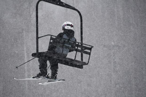 A lone skier takes the lift up the mountain during the opening day at Sunlight Mountain.