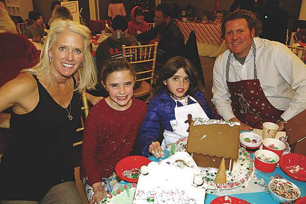 Bisque Jackson decorates gingerbread houses with her daughters Desi and Jaden and Frank Roddy.