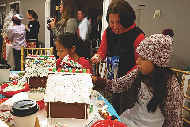 Chris Cohen admires the creative decorations by sisters Melissa and Alejandra on their gingerbread houses.