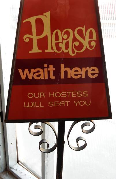 A wait to be seated sign that appears to be from the 1960s is part of the old relics that will be relocated to the new Wienerstube.