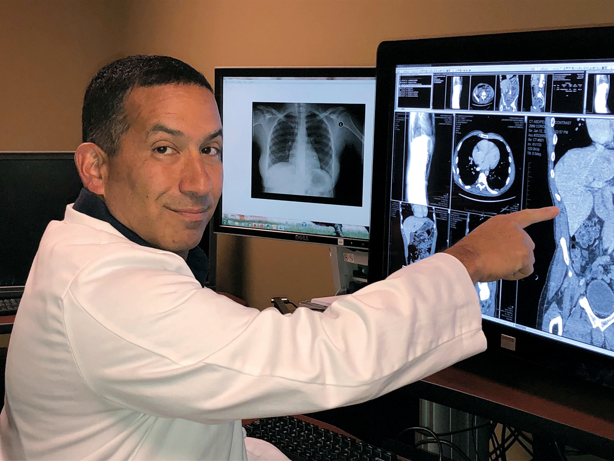 Dr. Andrew Fisher, radiologist, reads a CT scan of the abdomen and pelvis in the radiology department.